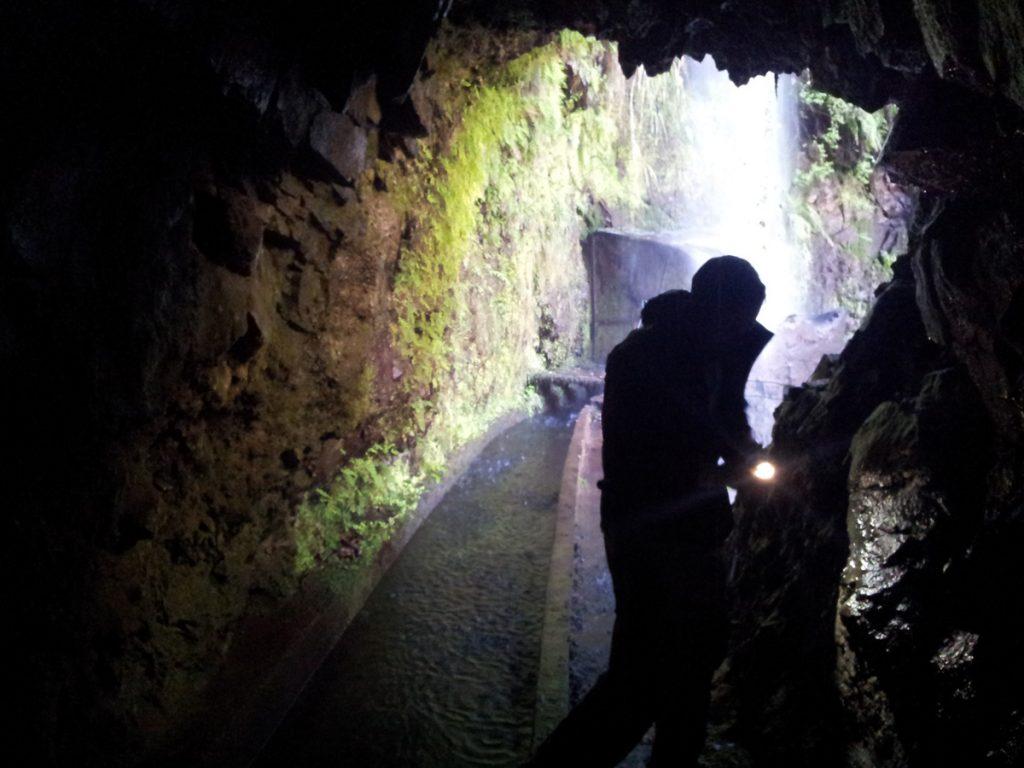 Unbedingt eine Taschenlampe mitnehmen (und eine Regenjacke, wie hier im Hintergrund zu sehen)! Die oft hunderte Meter langen Tunnel, hier an der Levada da Central nahe Lamaceiros im Inselnorden, verfügen fast nie über eine Beleuchtung und sind oft schlammig. Notfalls kann man sich auch mit einer Taschenlampen-App behelfen.